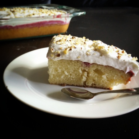 Fresh Raspberry Poke Cake with Homemade Whipped Cream Topped with Crushed Walnuts